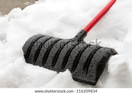 Shovel laying down against the snow.