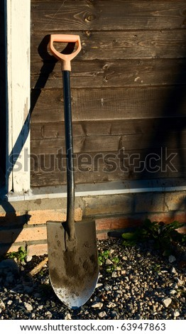 Shovel Leaning Against Wood Wall