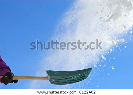 Shovel throwing snow in air