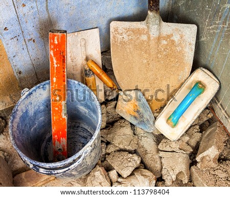 Shovel, trowels and other masonry tools in the corner of an unfinished concrete wall