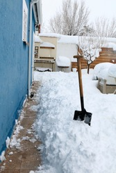 shovel used to remove snow. Snow removed with a shovel from the wall of a house to avoid humidity. The storm Filomena leaves half a meter of snow in Madrid