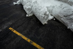Shoveled Snow on black Tarmac and yellow Marking Stripes - Concept for wintery Road Conditions