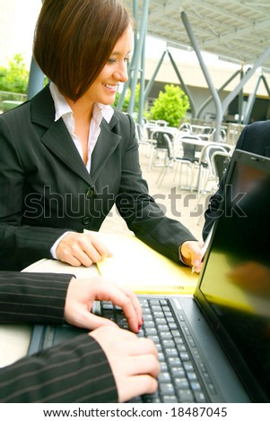 show of smiling business woman writing with hand of other woman typing on laptop on foreground