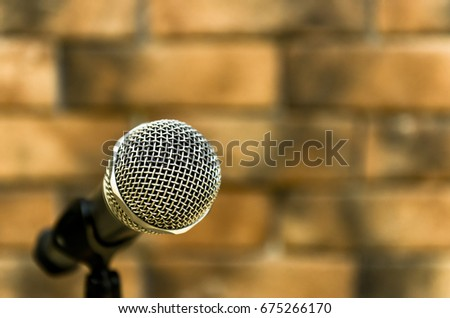 show your voice by metallic microphone beside the brick wall #675266170