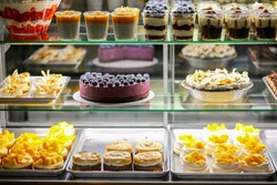Showcase with cheesecake, cakes, muffins, macaroons and pastries in the store. Sweets in the fridge for the holiday. Cakes and pastries for every taste.