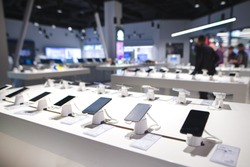 Showcase with smartphones in the modern electronics store. Buy a mobile phone. Many smartphones on the shelf of the technology store