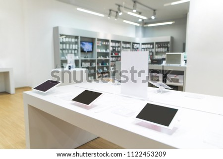 Showcase with tablets in the light modern tech store. Tablets on a showcase in a light electronics store.