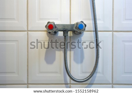 shower faucet turning knob, blue for cold and red for warmth Generic knobs for adjusting water temperature in the bathroom. tiled wall