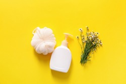Shower gel with bast wisp and chamomile flowers on color background