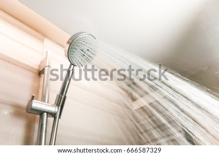 Shower head with refreshing water droplets spraying down in bathroom - Shutterstock ID 666587329