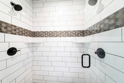 Shower stall with decorative tile walls outline and opened transparent glass door. There is a wall mounted shower fixtures on a white subway tile walls with brown patterned tile outline in the middle.
