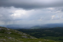 Showers in low mountains: spacious Chatyr-Dag middle plateau under the rain clouds. Rainy day in the highlands of Crimea
