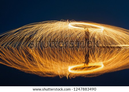Stock Photo Showers of glowing sparks from spinning steel wool.fire Steel wool on salt field at after sunset blue hour,