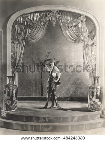 Showgirl posing under archway