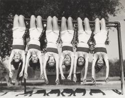 Showgirls hanging from monkey bars