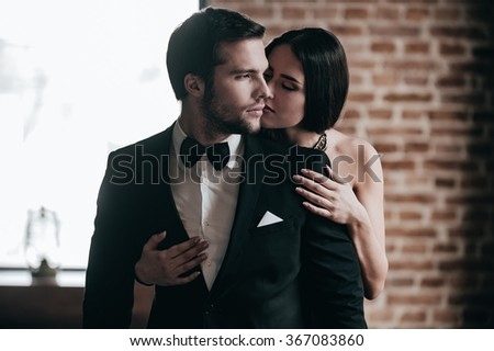 Showing her love. Close-up beautiful young woman standing behind her boyfriend wearing suit and giving him a kiss in cheek #367083860