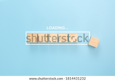 Showing loading bar with wood cube on blue background. Wooden blocks with the word LOADING in loading bar progress. Concept loading.