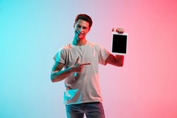 Showing on tablet screen. Young caucasian man's portrait on gradient blue-pink studio background in neon light. Concept of youth, human emotions, facial expression, sales, ad. Half length, copyspace.