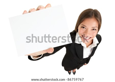 Showing sign - woman holding big business card / paper sign with copy space. Sign and businesswoman face both in focus. High angle full length view of happy smiling woman isolated on white background.