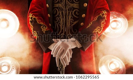 Showman. Pose, hands rest on stick. White gloves and beautiful sleeve of his coat, smoke on background of the spotlight #1062295565