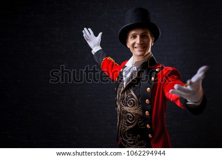 Showman. Young male entertainer, presenter or actor on stage. The guy in the red camisole and the cylinder. Bright tailcoat, suit