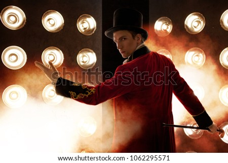 Showman. Young male entertainer, presenter or actor on stage. The guy in the red camisole and the cylinder, smoke on background of the spotlight
