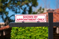 Shown By Appointment Only real estate sign on wooden post. Blurred green landscaping and clay tile roof background