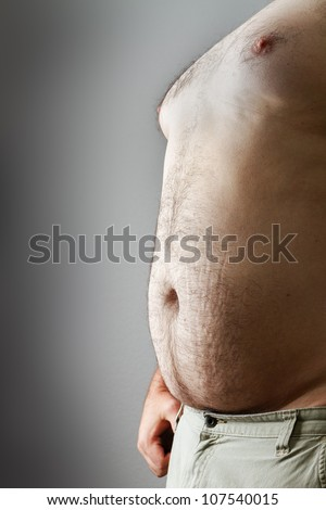 Shows too much food from either too much unhealthy eating , beer belly or just lack of exercise. includes stretch marks and some hair. - stock photo