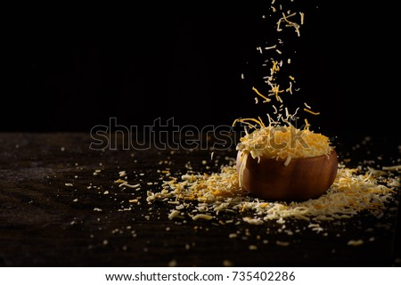 Shredded cheese being tossed into small wooden bowl.