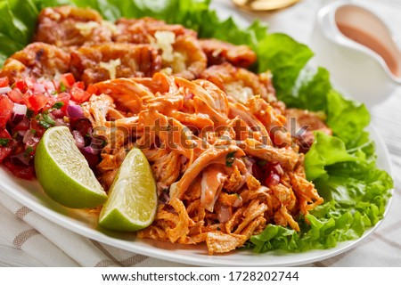 Shredded chicken with buffalo sauce, pico de gallo, lime wedges served with fried plantains on a white plate with fresh lettuce, on a white wooden table, close-up Foto stock ©