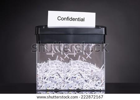 Shredded destroying confidential document over black background