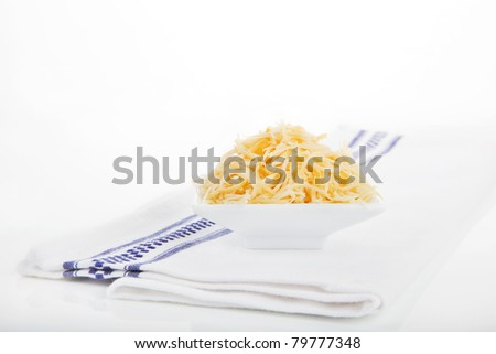 Shredded gouda cheese in white bowl on white towel isolated on white background.
