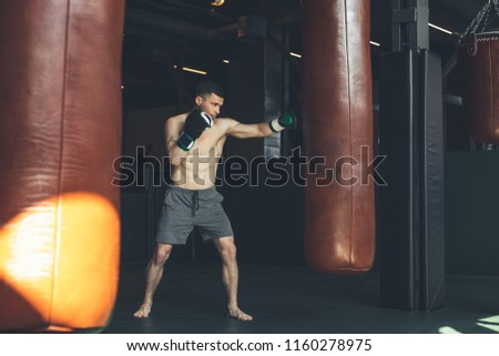 Shredded man is boxing with punching bags inside. He is hitting equipment with cross kick. Combat workout for strength and endurance concept #1160278975