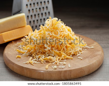 Shredded mozzarella and red cheddar cheese on wooden cutting board