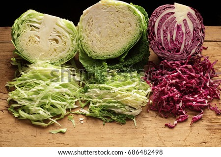 Shredded red, green and Savoy cabbage,   on wooden background