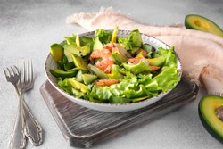 shrimp and avocado salad in a ceramic plate on a light table