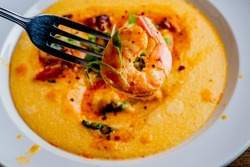 Shrimp and Grits Classic American Diner Style Breakfast/Brunch menu item.  traditional low country southern staple.  Homemade grits and old bay seasoned jumbo shrimp topped w/ spices and micro greens.