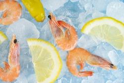 shrimp and lemon wedges lie on ice