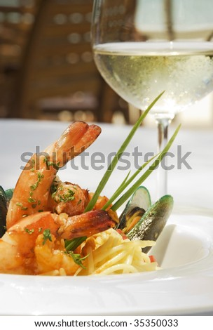 Shrimp and oyster spaghetti served in a white ceramic plate and accompanied with a glass of a white wine.