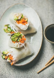 Shrimp and vegetable rice paper spring rolls with sauce and chopsticks, top view, selective focus. Asian cuisine, clean eating, vegetarian, dieting food concept
