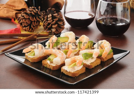 Shrimp avocado canapes on mini toasts with red wine