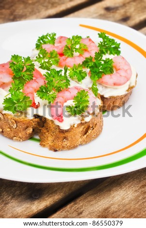 Shrimp crostini with parsley on a plate (shallow dof)