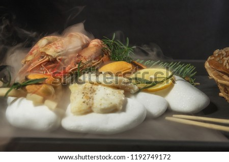 Shrimp, fish, mussel, fillet on red-hot pebble with steam, seafood chopsticks, organic food, raw food