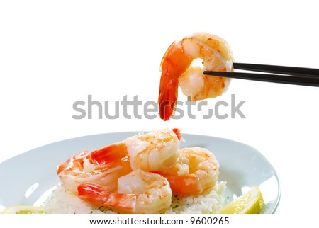 Shrimp held by chop sticks with more on a plate with rice