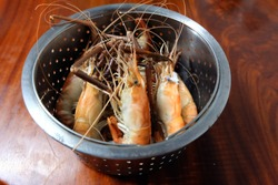 Shrimp in a stainless steel container on a wooden table prepared for serving.