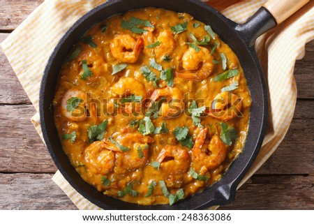 Shrimp in curry sauce in a pan close-up. horizontal view from above