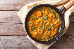 Shrimp in curry sauce in the pan. horizontal view from above
