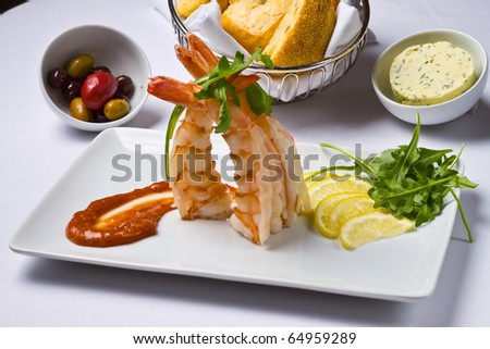 Shrimp, lemon. cocktail sauce, olives, and bread on a white plate