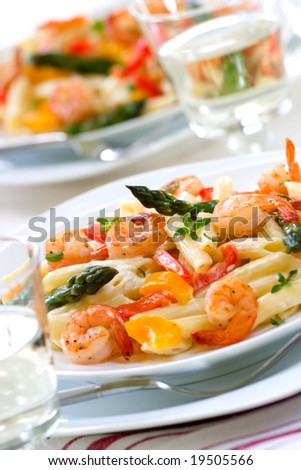 Shrimp Penne (tube-shaped pasta) with asparagus, bell pepper, origan and creamy Alfredo sauce . Shallow DOF