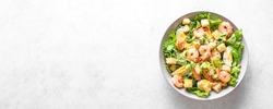 Shrimp Salad. Seafood Caesar Salad on white stone background, top view, copy space.
